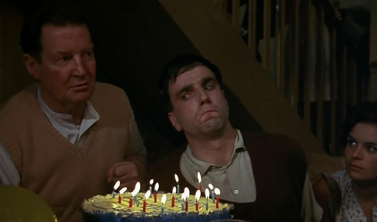 He is both the cake and the candles. Who are those other two looking at?