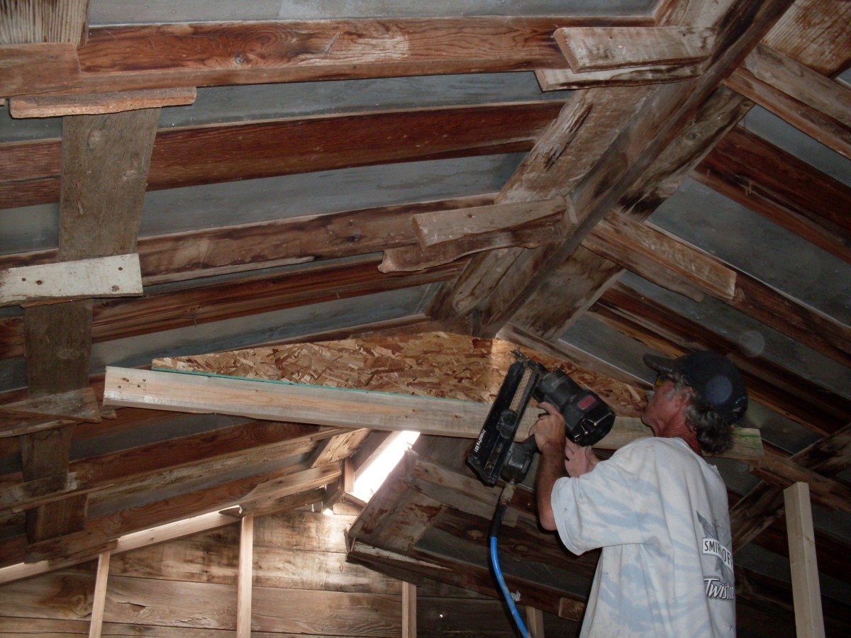 Use a nail gun to fasten brace to the rafters, but not to the 2x6 brace. The 2x6 is there only to hold things together until the triangle brace is in. The triangle sits on it. Shoot nails in at an angle through all the layers, deep into the rafters.
