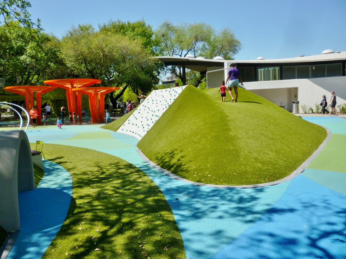 Raised area in children's area with rock wall on one side & wide slide on other side