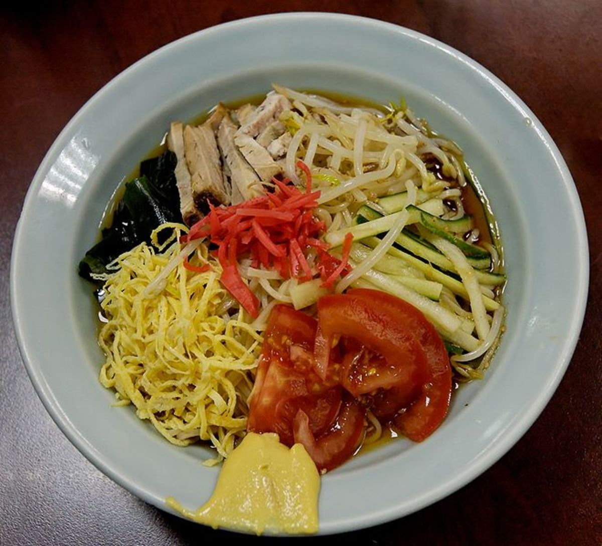 Ramen in Paris -- This cold dish is of noodles, pork, omelette shreds, wakame seaweed and cucumber in a vinegar base sauce or soup. (public domain)