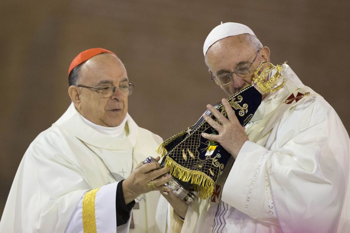 Pope Francis  kissing an image of  the Virgin of Aparecida, a black Mary at the World Youth Day Mass July  2013.