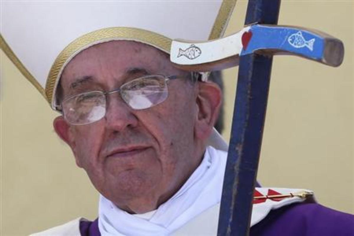 Pope Francis with a cross with the image of a fish on it.