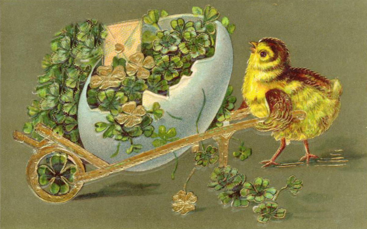 Vintage Easter chick pushing cart made of a broken egg and filled with four-leaf clovers