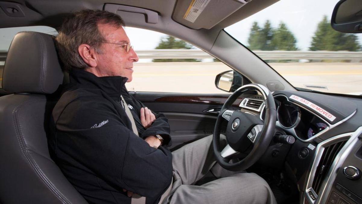 Car with no gads on steering wheel. General Motors' Super Cruise could allow the car to drive itself on long, monotonous stretches of highway – leaving the driver free to relax.