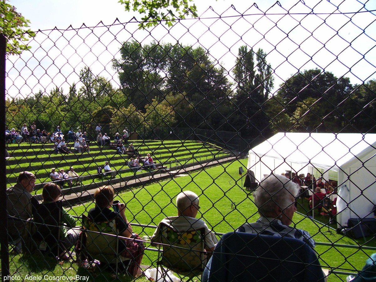 On the sunny grass tennis courts near the rose gardens, people sit to enjoy the free brass band concert organised by the Friends of Ashton Park.