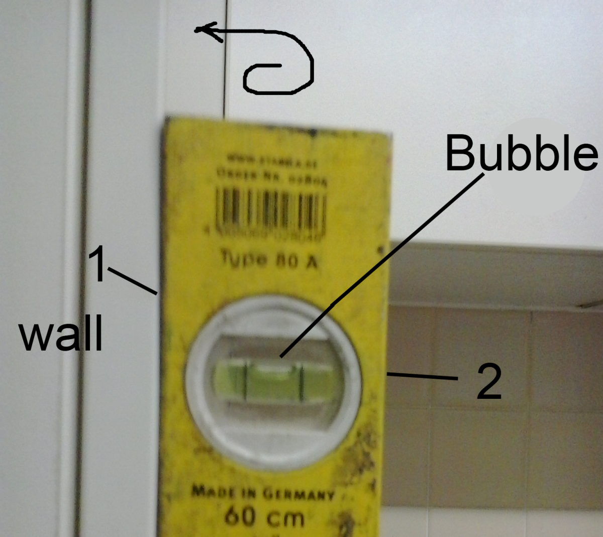 Diagram showing level against a wall. Bubble should be in the same position when the side against the wall is reversed - i.e. when either side 1 or 2 of level is against the surface being checked bubble position should be the same.
