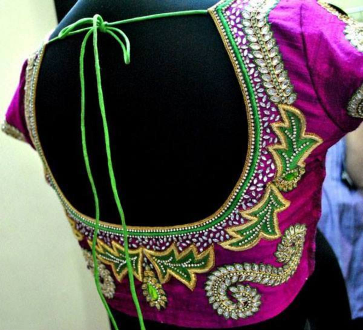 Magenta blouse with a green embroidery and embellishment.