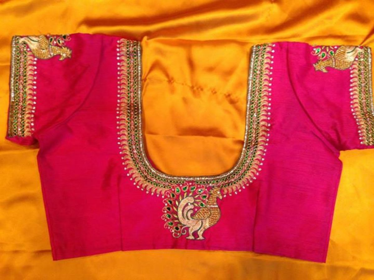 A hot pink choli blouse with a U-shaped neck with embroidery and embellishment.