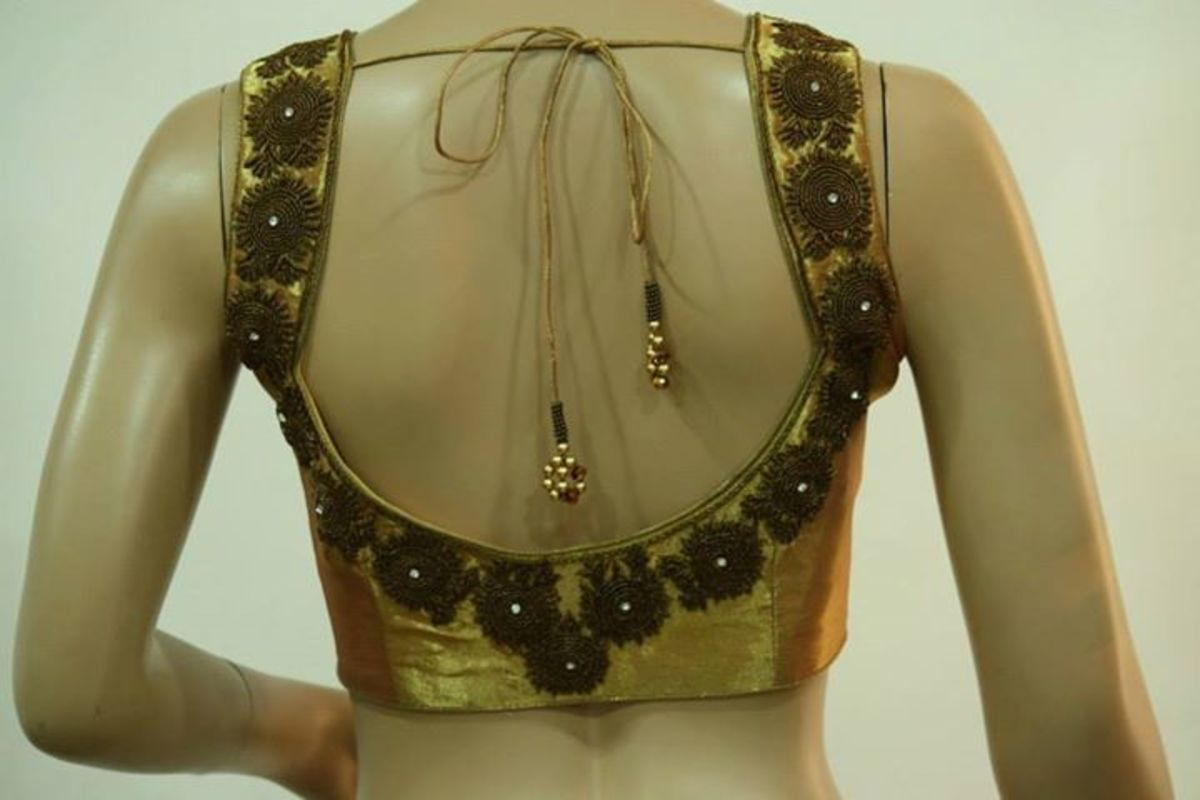 A deep back neck on a golden blouse—sleeveless choli design.