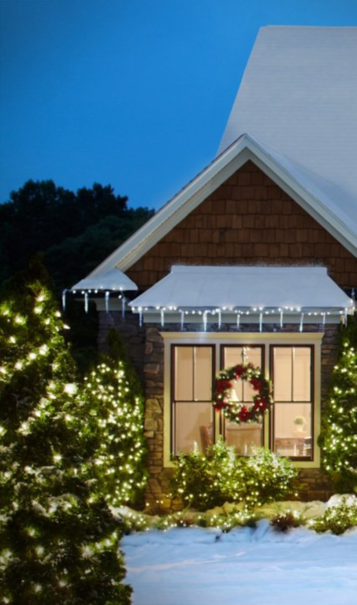 Holiday Wreaths on Windows on Classic Victorian Showcased Lighted at Night on a Bay Window