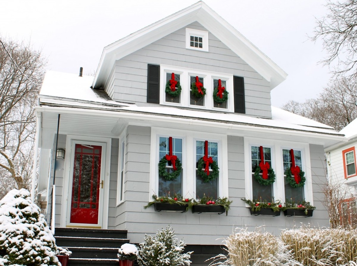 Classic Victorian Two-Story House With Evergreen Holiday Wreaths on the Windows