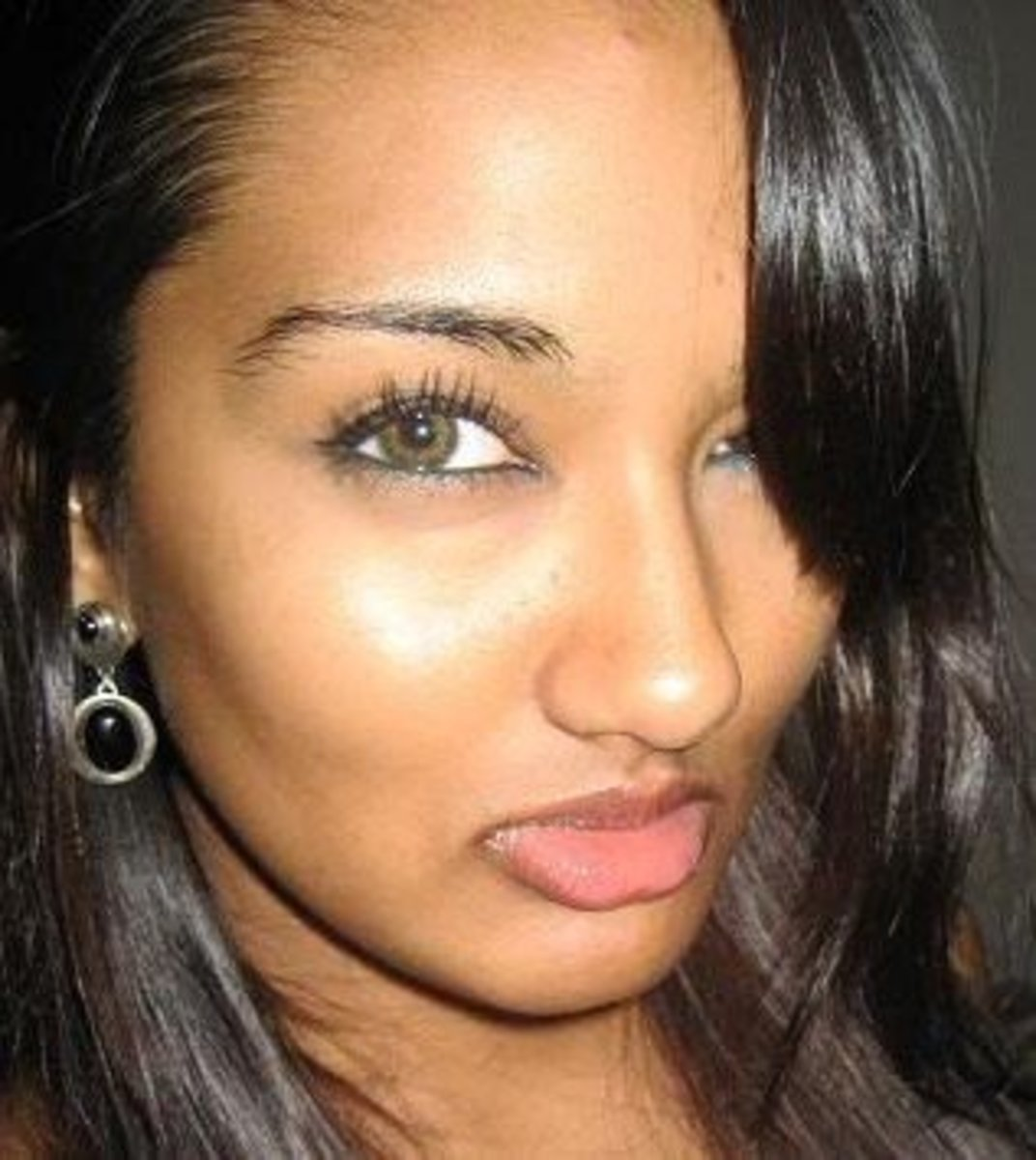 Tanned girl wearing Freshlook Colorblend contacts in Green.