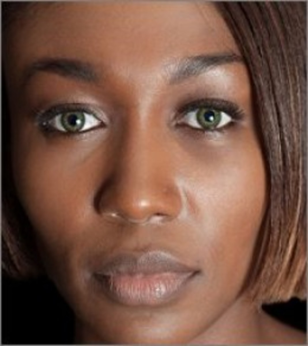 Gorgeous dark-skinned woman wearing Acuvue Hazel Green contacts.