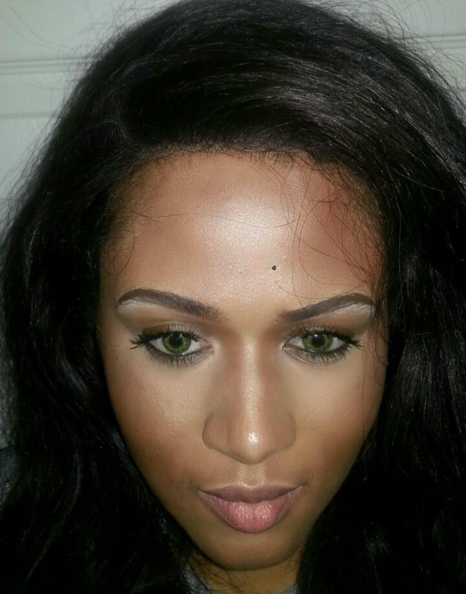 Dark-skinned girl wearing Freshlook's Gemstone Green contact lenses.