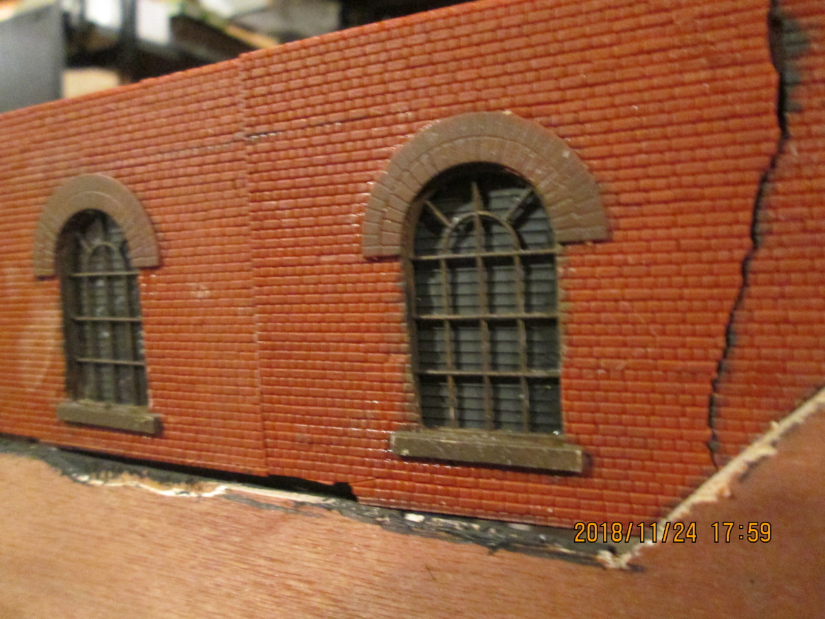 Under-line factory windows with plastic frames from a Wills' pack backed by Humbrol matt anthracite painted plastic sheet either side of the windows. Two frames backed with clear plastic 'glazing'. War damage shown by 'cracked' wall .