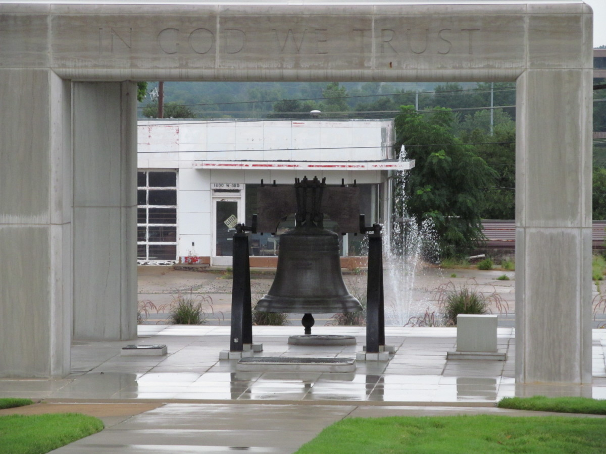 In God We Trust - Liberty bell sits in front of a closed gas station, under a marble cover...while the Little Rock Nine are out in the weather...