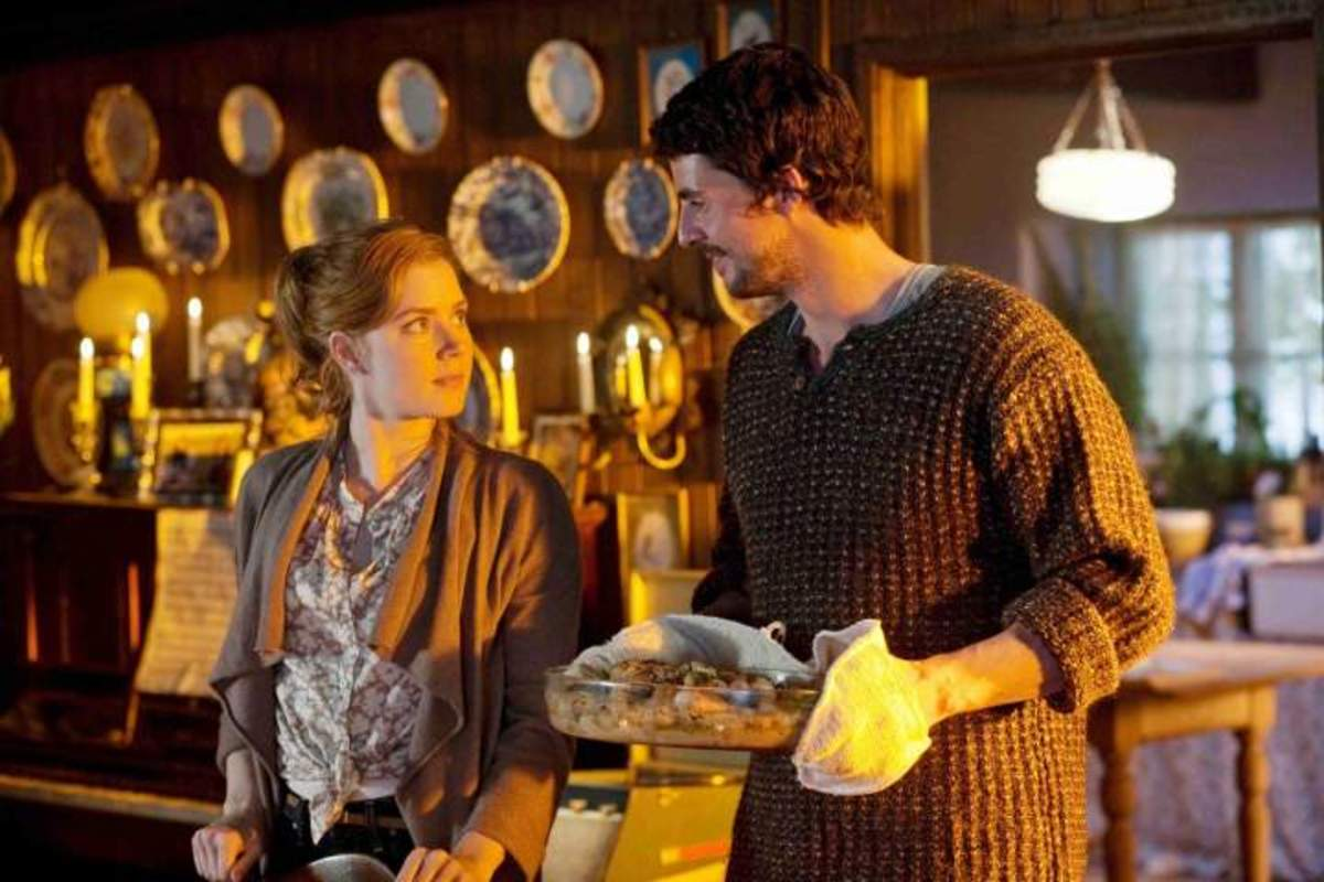 "Declan bringing his cooking into the dining room after Anna sets the table in the couple's home that has a room for them. Scene from the movie ""Leap Year""."