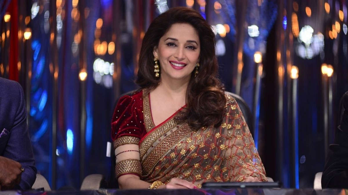 Madhuri Dixit looking beautiful in a maroon velvet blouse with puffed sleeves and a saree of beige net.