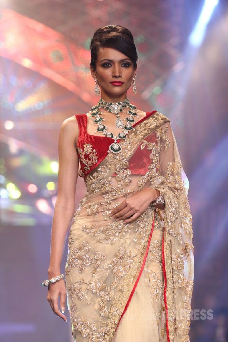 A red velvet sleeveless blouse with a golden beige designer saree, on the runway.