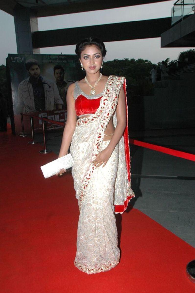 A bright red designer velvet saree blouse with a white saree design.
