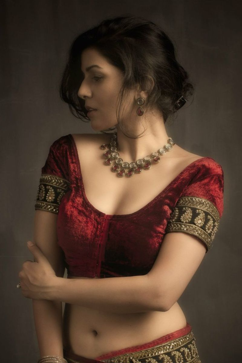 A maroon velvet blouse for saree with a black sleeve border.