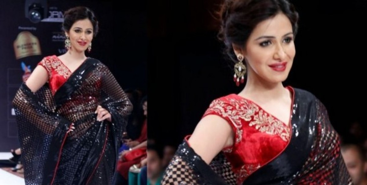 A red velvet blouse with gold embroidery, worn with a black saree.