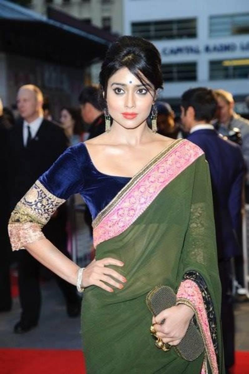 Deep blue velvet saree blouse with an olive green saree