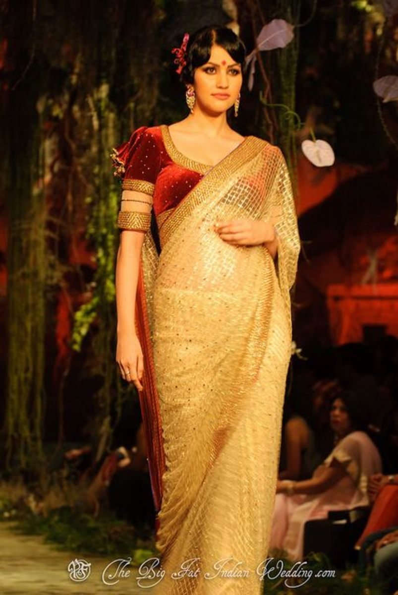 A reddish-maroon velvet saree blouse worn with a gold designer saree.