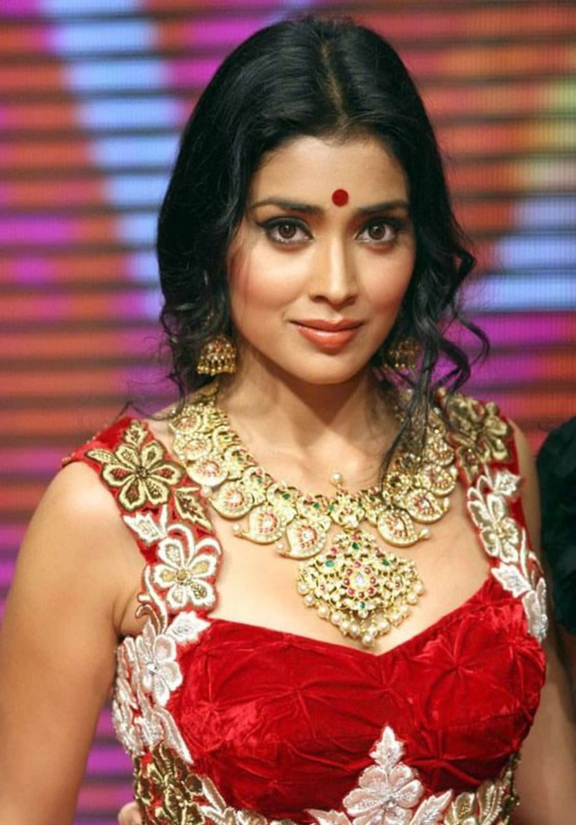A Bollywood actress in a sexy, sleeveless, bright red velvet sari blouse with embroidered shoulders.