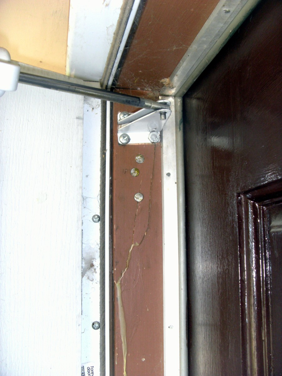 Broken door frame, repaired with nails and long screws