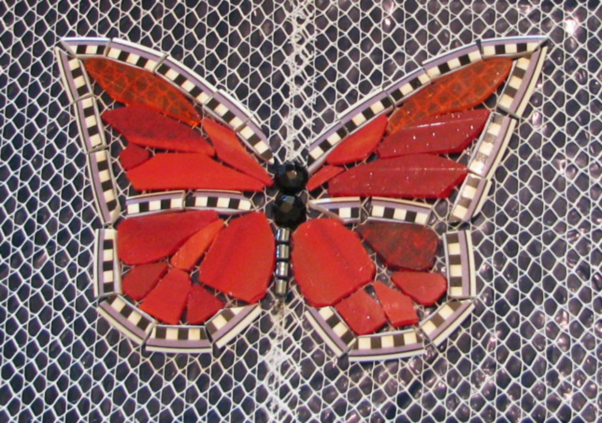 The edge is plate rim, red-orange stained glass, black faceted glass beads nipped in half, hematite bead body.  Will be grouted with black grout.