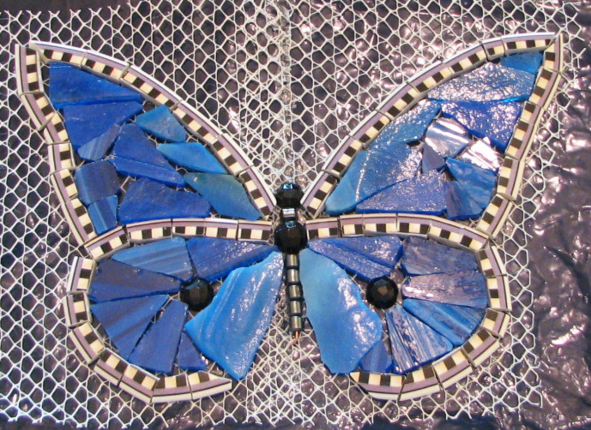 Edge is a plate rim, blue stained glass, black faceted glass beads cut in half, hematite beads.  Imagine it grouted in black grout.