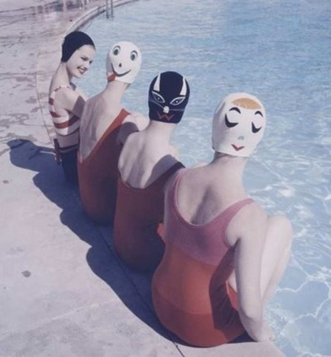 four vintage swimmers with swim caps