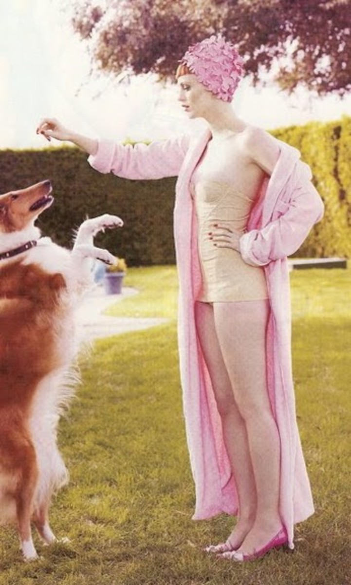 lady wearing a pink swim cap, pink robe and white one piece swim suit feeding a treat to a dog who is jumping up for the treat