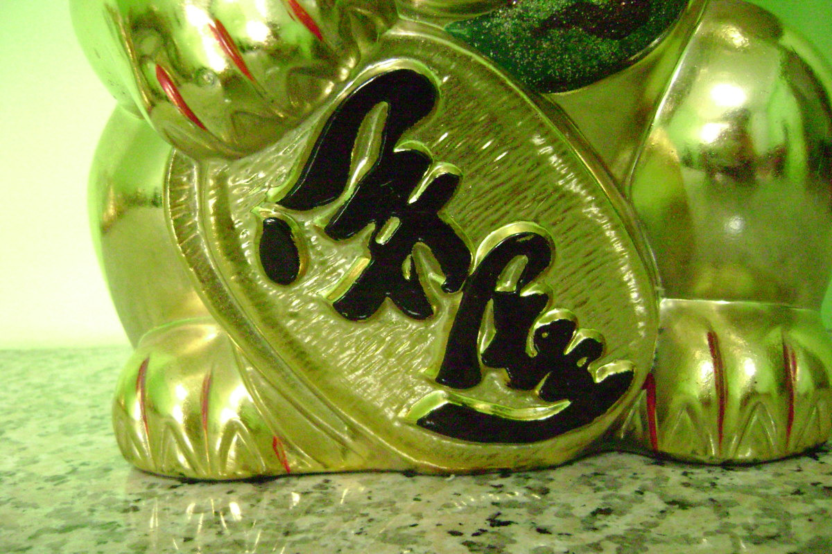 Instead of a coin, the cat is holding a sign with auspicious wordings on it.