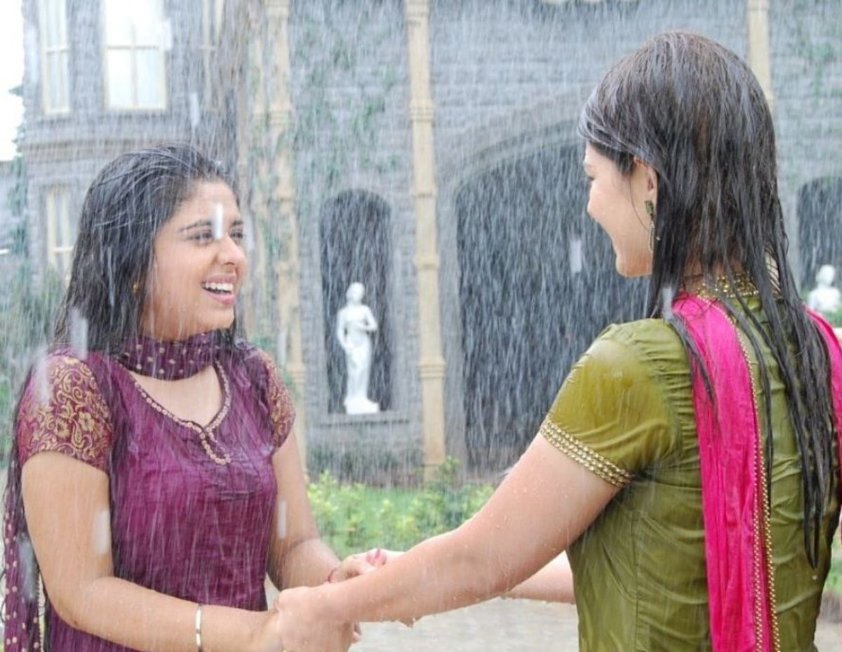 Divya and Nivedita dancing in the rain thinking of Siddharth