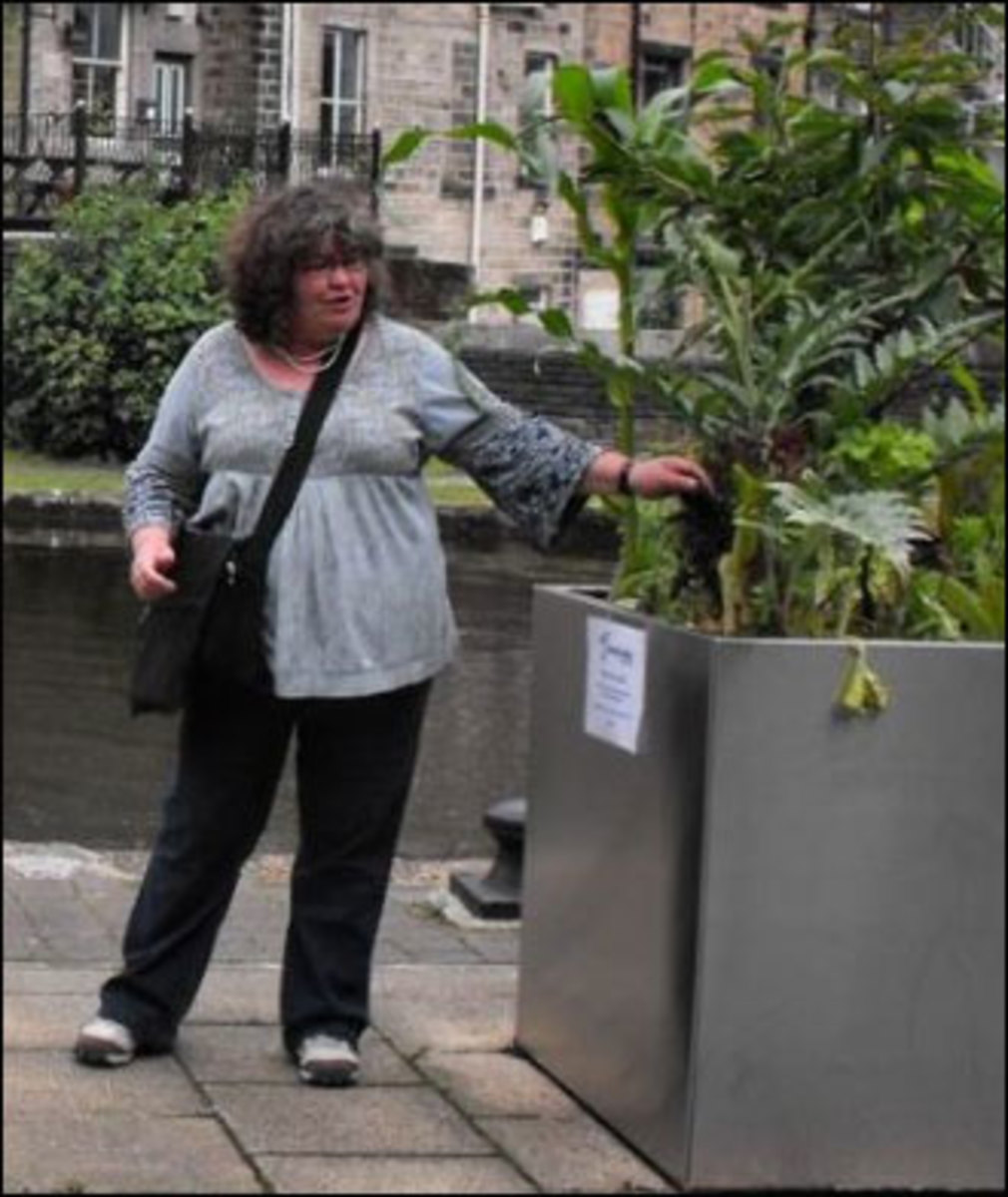 Mary Clear inspects one of the public vegetable containers.