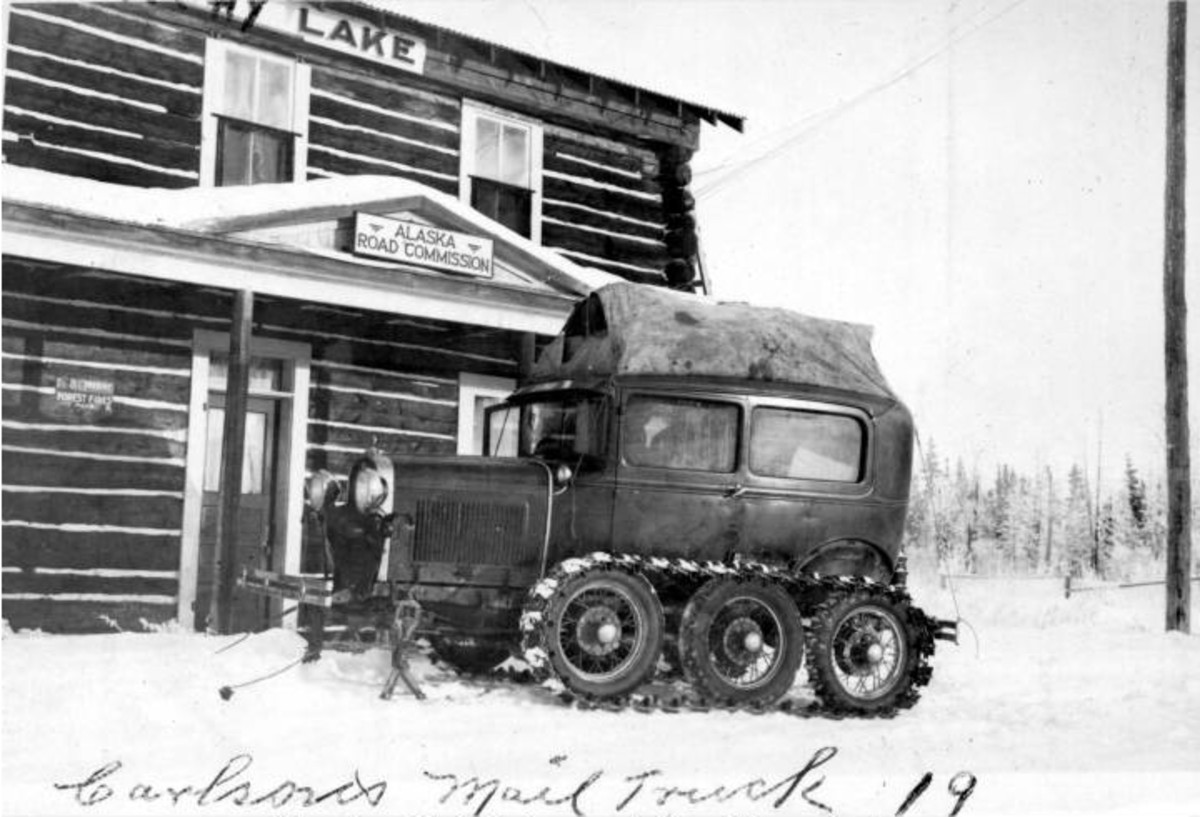 An Alaskan Highway Mail Truck, photo, taken 1919, parked in front of a Alaska Road Commision building.  In the public domain.