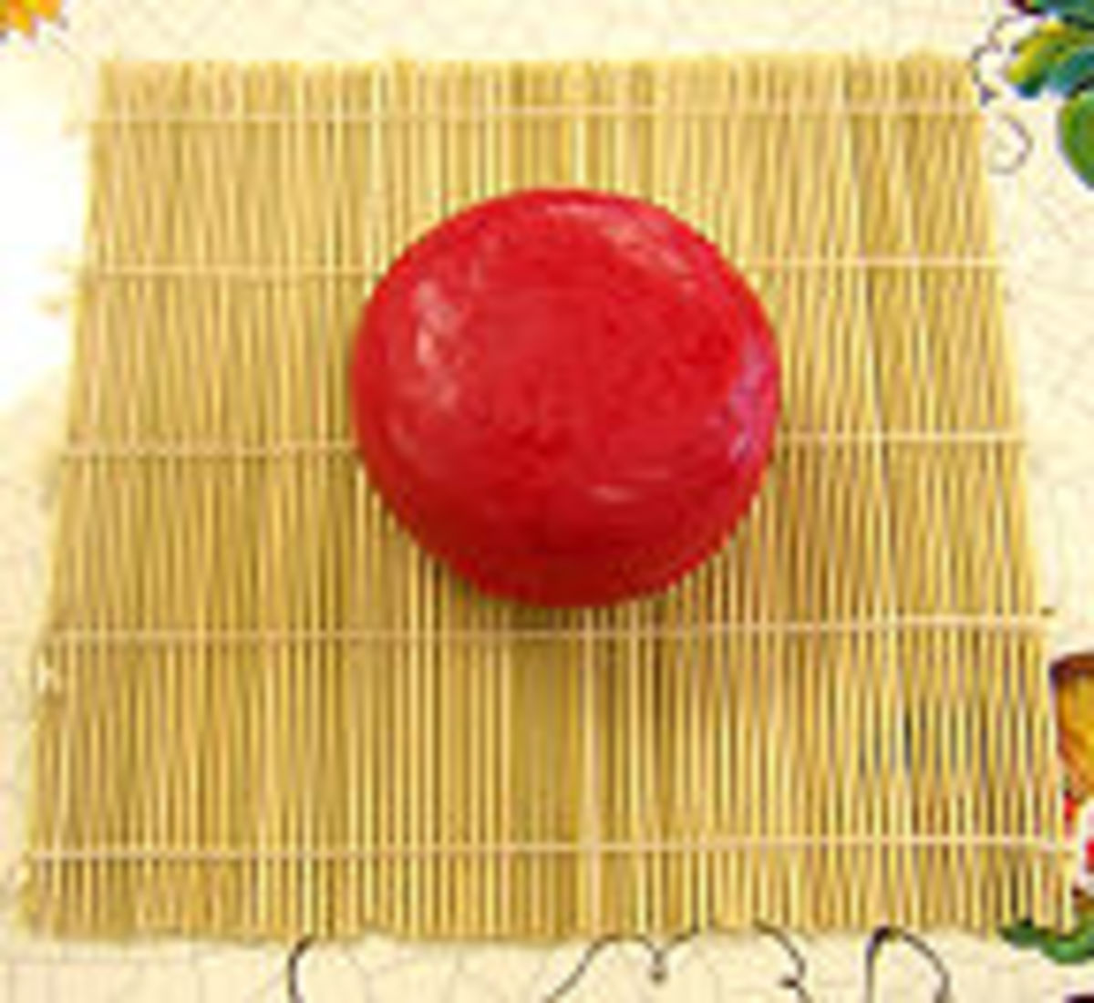 """In this image you see a """"waxed"""" cheese sitting upon a """"cheese mat""""."""
