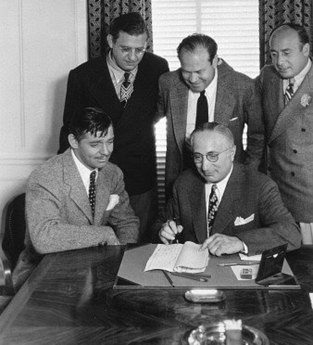 Clark Gable and Mayer seated, Selznick behind Gable