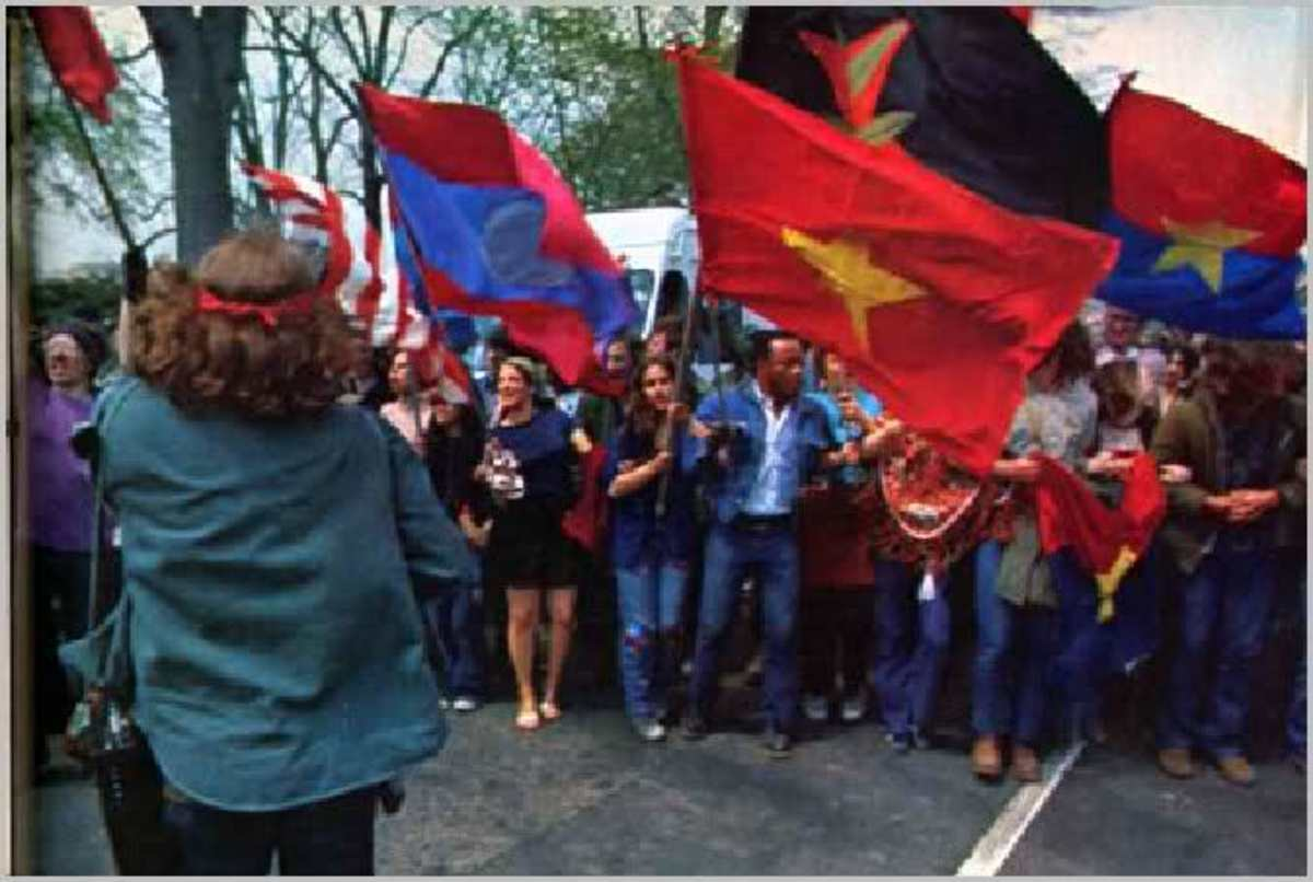 AMERICAN CITIZENS PROTEST THE VIETNAM WAR WAVING COMMUNIST FLAGS