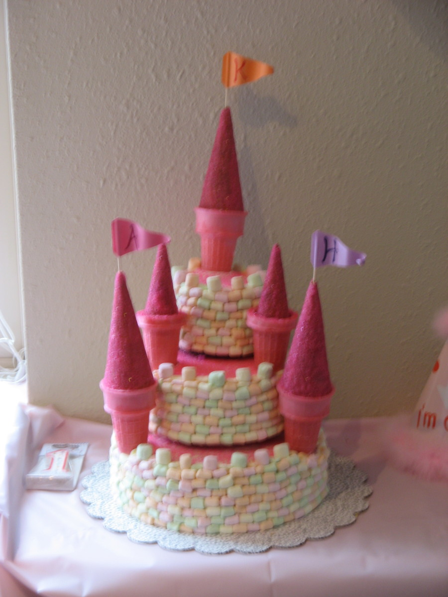 "Used cake and sugar cones (coated in corn syrup, rolled in pink sugar) with colored marshmallows (sliced in half) to create the ""bricks"" of the castle.  My first attempt at stacking cakes like a wedding cake, inspired by one I saw in a Parenting Mag."