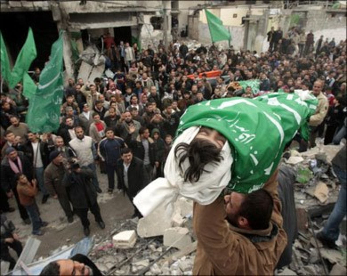 In the Gaza Strip region the lifeless body of a young casualty is carried through the streets