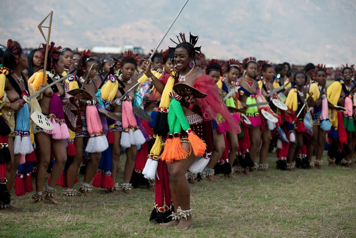 Members of the royal Swazi family dance with young girls dance at a traditional Reed dance ceremony at the stadium at the Royal Palace in Ludzidzini, Swaziland