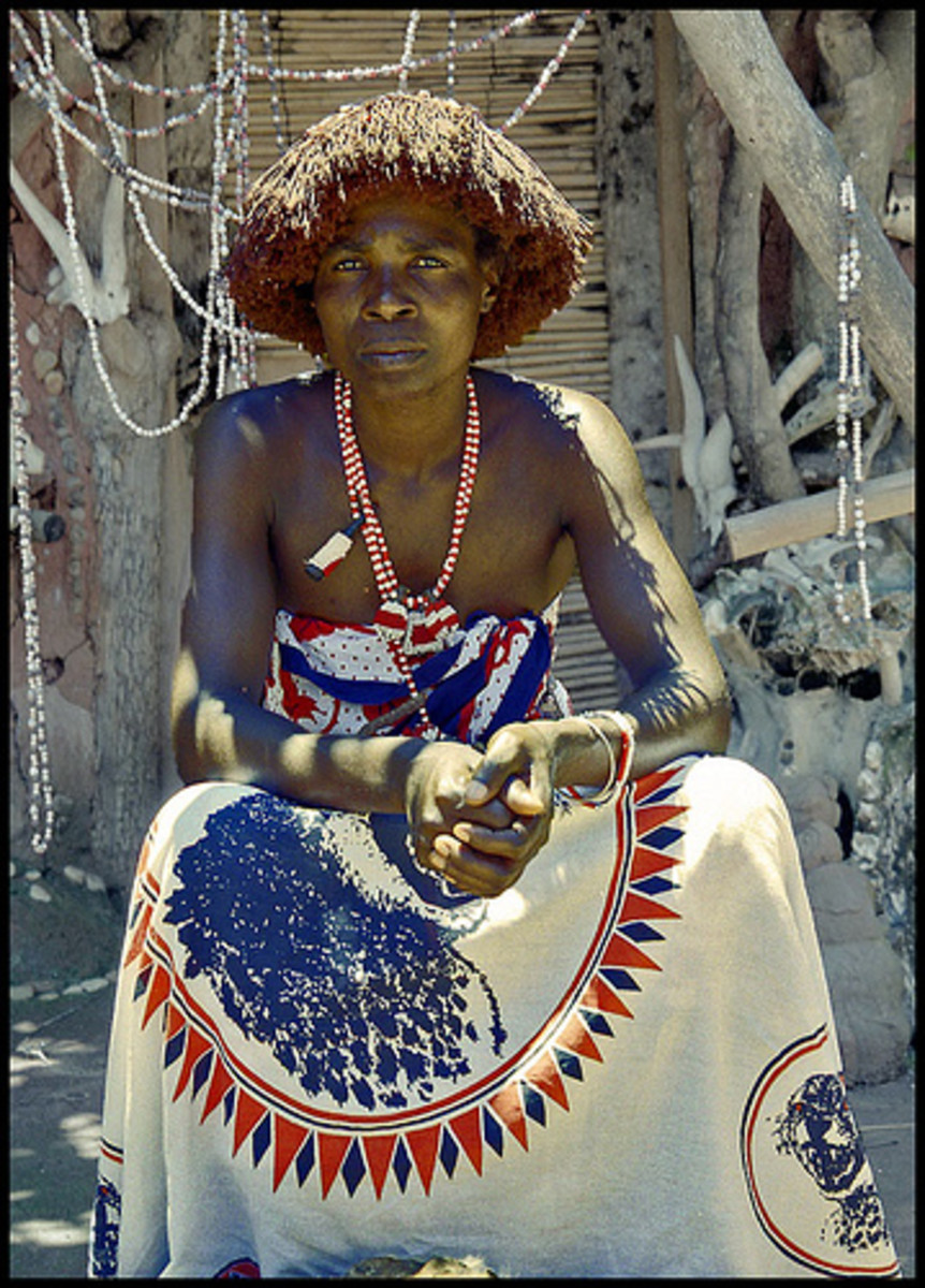A Shangaan man sitting next to her hud and wearing his hair the traditionally Shangaan way, and a cloth and beads