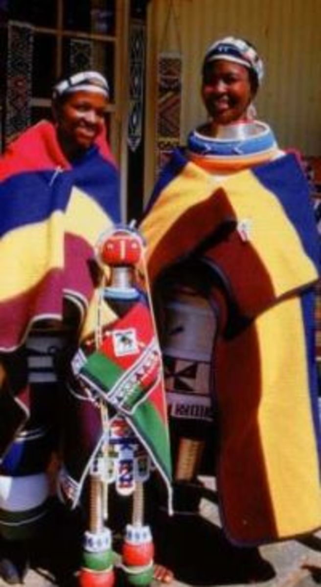 Ndebele Women and clad in their traditional Blanket and colors and standing next to their 'tall' doll