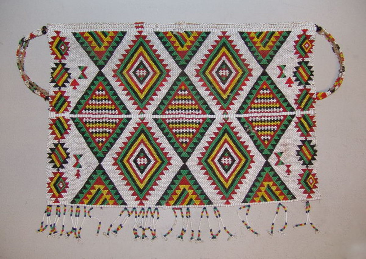 Zulu beaded apron made with tiny glass beadsDazzling geometric designs were created by use of the brick stitch. Triangles in this apron are recorded to represent traditional Zulu Shields