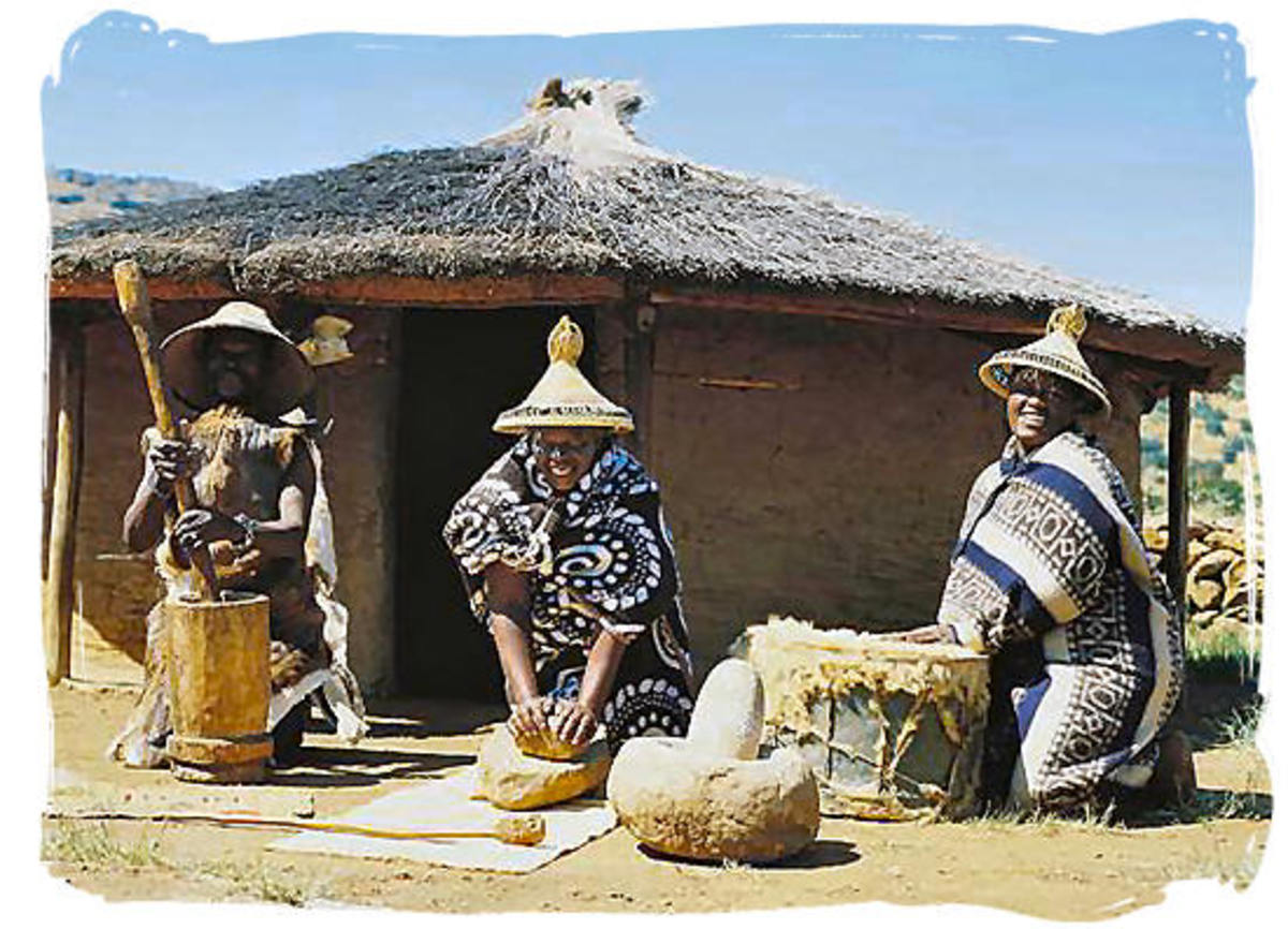 """Basotho People next to their hut and adorned in their traditional garb(Their hats are called (""""Modianyeho"""")"""
