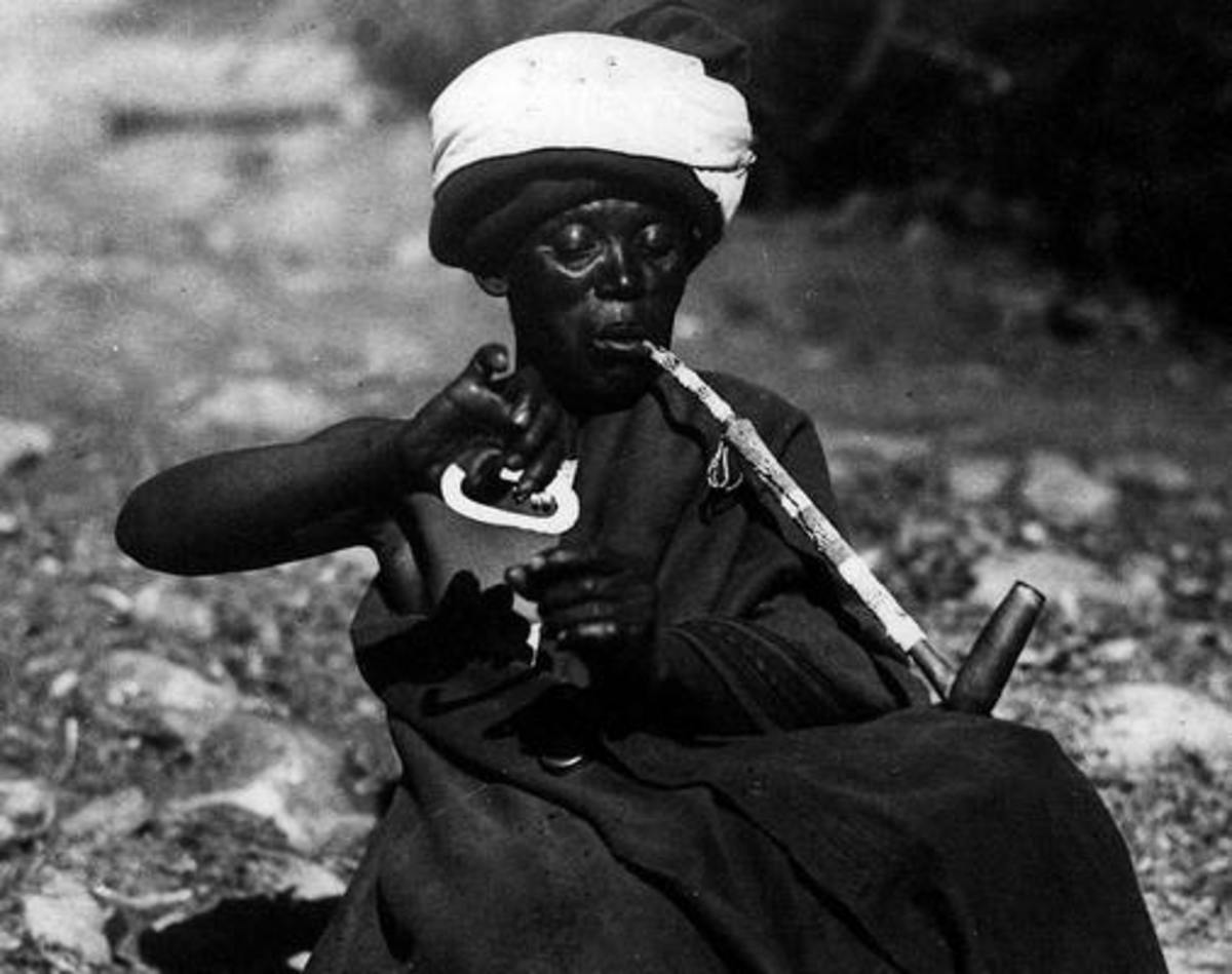 A woman lighting her pipe using a flint