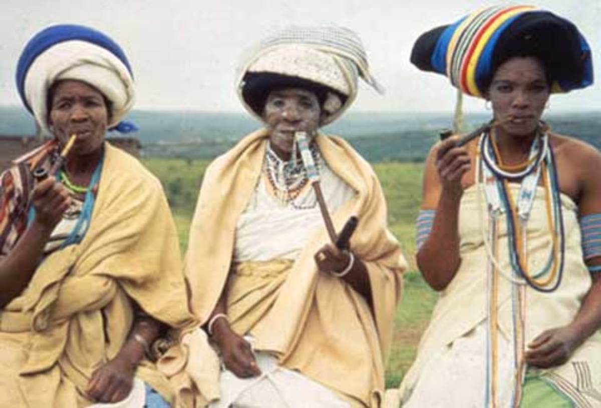 Xhosa Women in their traditional garb  and smoking their pipes. The elegant beadwork on their pipes keeps the pipestems cool enough to handle